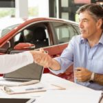 couple with salesman in car showroom