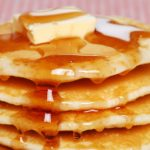 Four pancakes on a white plate covered in butter and syrup