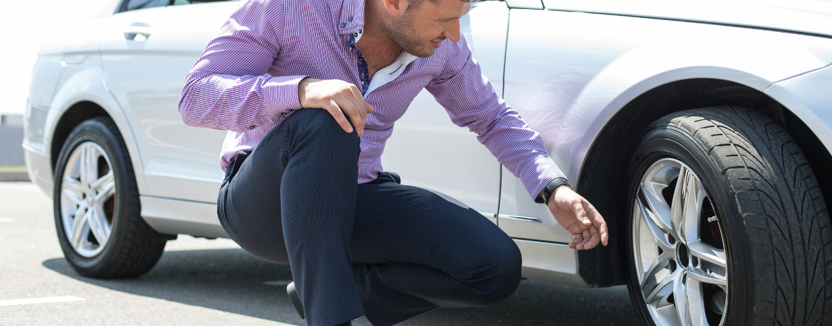 man looks at tire